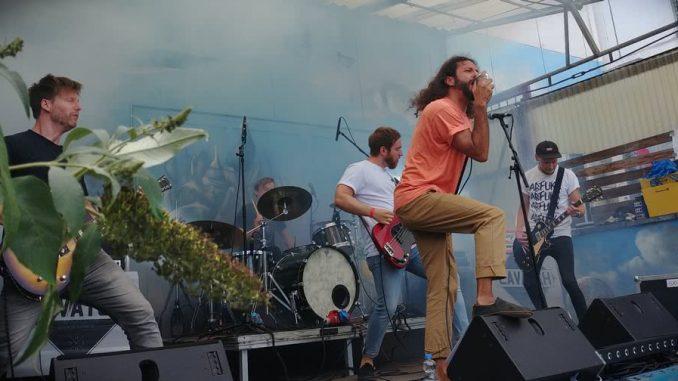 Lavatch auf der Bühne, 2x Gitarre, Bass, Schlagzeug und Gesang. Der Gitarrist wird von einer Blumenblüte verdeckt.