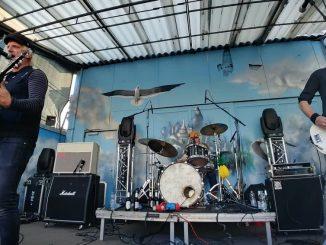 Shout-Outs, Gitarre, Schlagzeug, Bass, auf der Bühne. Auf die Wand im Hintergrund ist eine Möve gemalt.